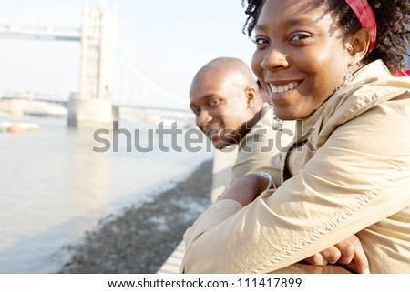 Portrait of an african american tourist couple visiting the Tower of London overlooking the river. - stock photo
