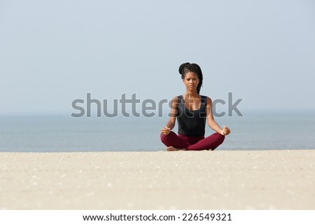 Portrait of an african american woman sitting at beach in yoga pose - stock photo