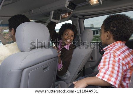 Portrait of an African American woman sitting in car with small boy in foreground - stock photo