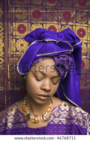 Portrait of an African American woman wearing traditional African clothing and closing her eyes in front of a patterned wall. Vertical format. - stock photo