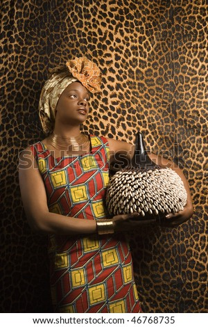 Portrait of an African American woman wearing traditional African clothing and holding a shekere in front of a patterned wall. Vertical format. - stock photo