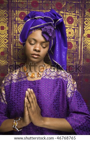 Portrait of an African American woman wearing traditional African clothing in front of a patterned wall and holding her hands in a prayer position. Vertical format. - stock photo
