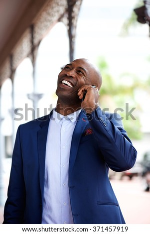 Portrait of an african businessman smiling and talking on mobile phone in city  - stock photo