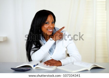 Portrait of an african student smiling and pointing to his left - stock photo