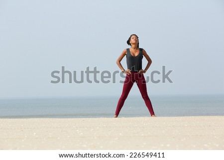 Portrait of an african woman doing yoga breathing exercise with hands on hip at the beach - stock photo