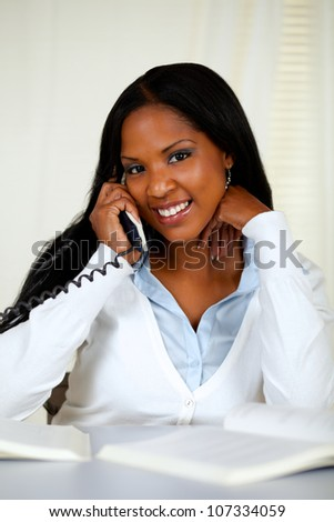 Portrait of an african young woman conversing on phone at home indoor - stock photo