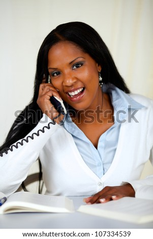 Portrait of an african young woman laughing and speaking on phone at home indoor - stock photo