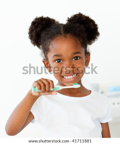 Portrait of an Afro-american girl brushing her teeth in the bathroom - stock photo