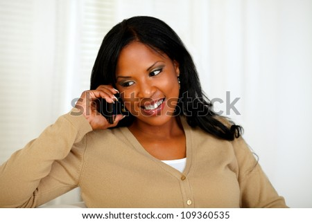 Portrait of an afro-American woman conversing on mobile phone at home indoor - stock photo