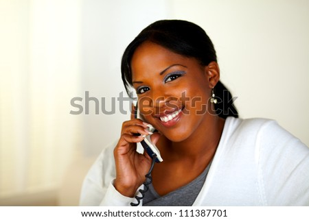 Portrait of an Afro-american woman looking at you on phone at home indoor. With copyspace