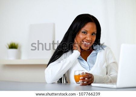 Portrait of an afro-american young woman drinking a healthy orange juice while is looking to you in front a laptop at home indoor - stock photo