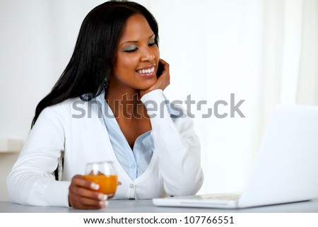 Portrait of an afro-american young woman looking to laptop screen  at soft colors composition - stock photo