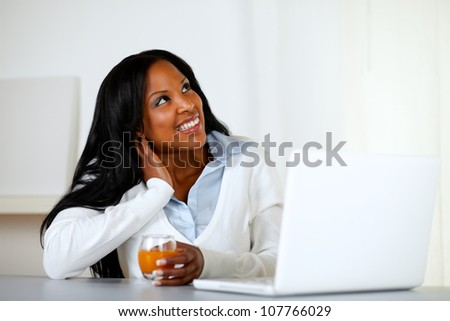 Portrait of an afro-american young woman looking up while is drinking an orange juice an having fun on laptop computer at home - stock photo