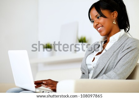 Portrait of an afro-american young woman using laptop at home indoor - stock photo