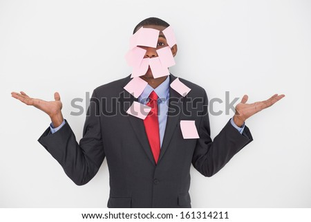 Portrait of an Afro businessman covered in blank notes over white background - stock photo