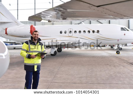 Portrait of an aircraft mechanic in a hangar with jets at the airport - Checking the aircraft for safety and technical function