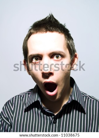 Portrait of an amazed young man - stock photo