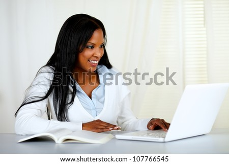 Portrait of an american young black woman working on laptop at home indoor - stock photo