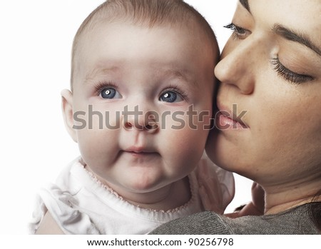 Portrait of an angelic baby with blue eyes and her mom.  Isolated against white background