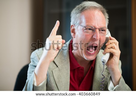 Portrait of an angry businessman yelling at phone