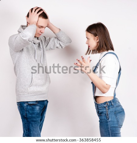 Portrait of an angry couple shouting each other against white background