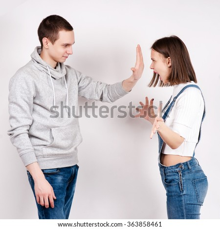 Portrait of an angry couple shouting each other against white background - stock photo