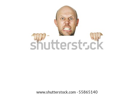 Portrait of an angry man peeking over a wall - stock photo