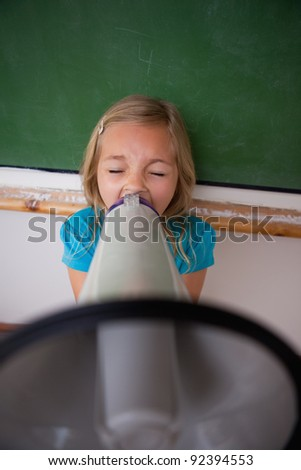 Portrait of an angry schoolgirl screaming through a megaphone in a classroom - stock photo