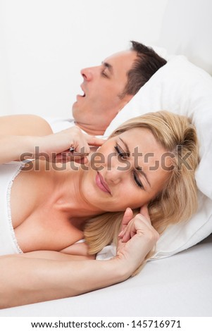 Portrait Of An Angry Woman Awaken By Her Boyfriend's Snoring - stock photo