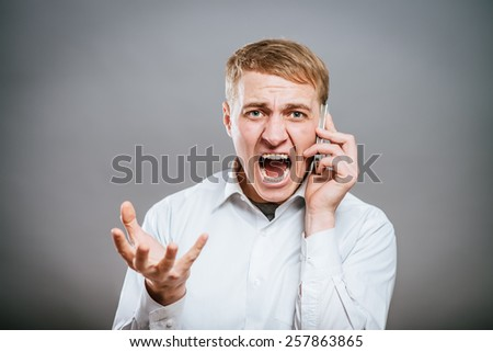 portrait of an angry young man shouting using a mobile  - stock photo