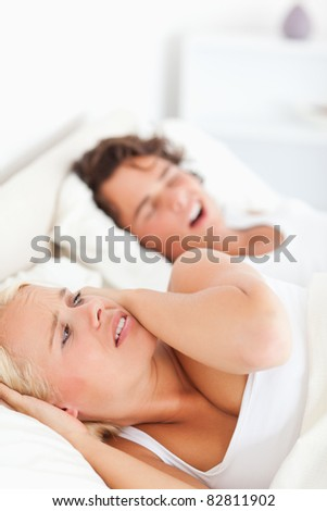 Portrait of an annoyed woman awaken by her fiance's snoring in their bedroom - stock photo