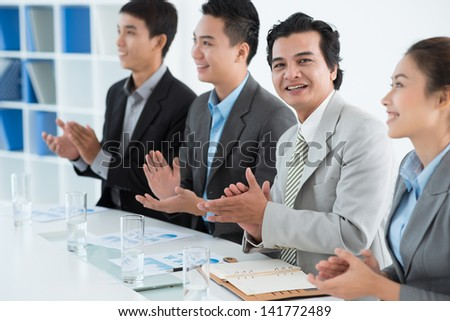 Portrait of an applauding businessman on the foreground