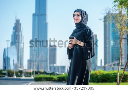 Portrait of an Arab businesswomen. Arab businesswomen in hijab talking on cell phone on the street on a background of skyscrapers of Dubai. The woman is dressed in a black abaya - stock photo