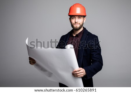 Portrait of an architect builder studying layout plan of the rooms, serious civil engineer working with documents on construction site.