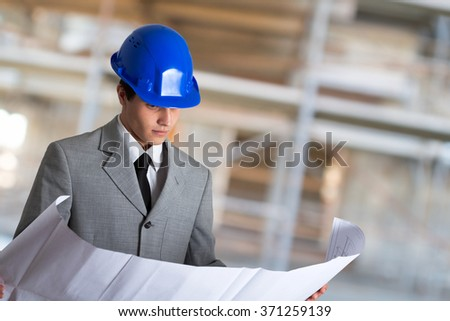 Portrait of an architect reading a drawing in front of a construction site - stock photo
