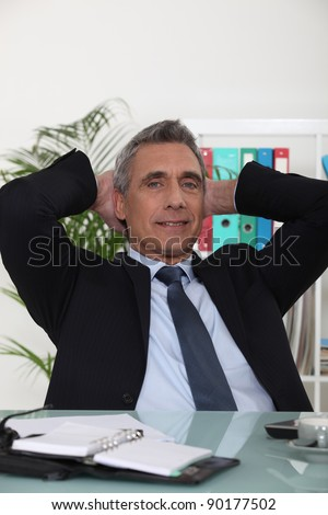 Portrait of an arrogant businessman with his hands behind his head - stock photo