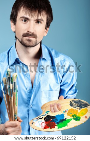 Portrait of an artist holding his brushes and paints. Shot in a studio. - stock photo