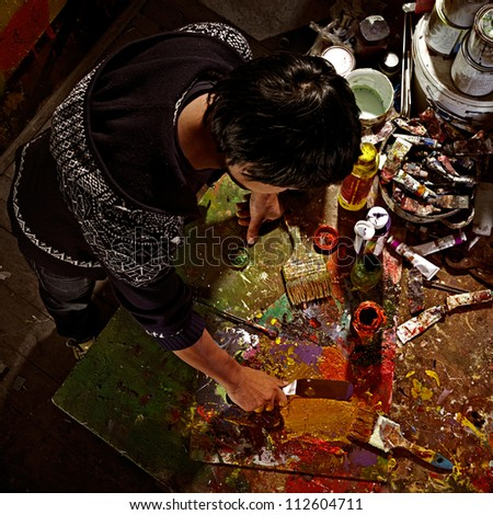 Portrait of an artist painting on easel. Shot in a art studio. - stock photo