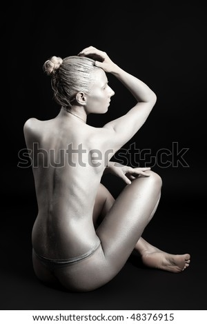 Portrait of an artistic woman painted in metal style. Shot in a studio.