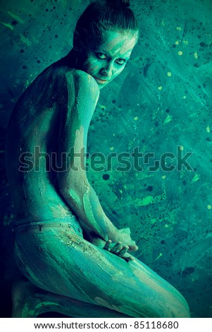 Portrait of an artistic woman painted with clay. Shot in a studio over black background. - stock photo