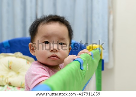 Portrait of an asian baby in playpen