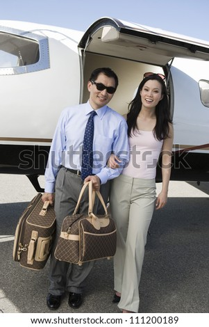 Portrait of an Asian business couple standing together with airplane in the background at airfield - stock photo