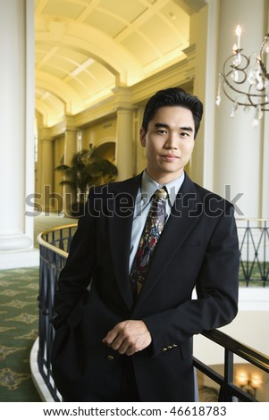 Portrait of an Asian business man leaning on a rail in an upscale hotel. Vertical shot. - stock photo