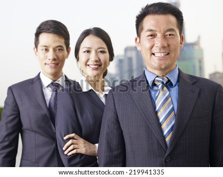 portrait of an asian business team, focus on the man in front. - stock photo