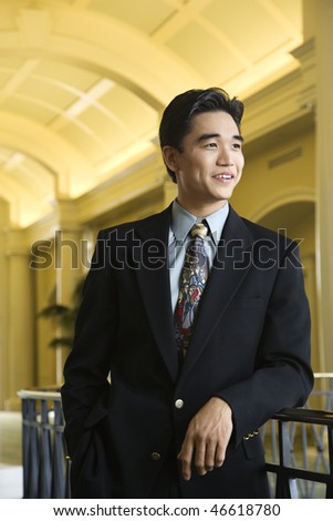 Portrait of an Asian businessman leaning on a rail in an upscale hotel. Vertical shot. - stock photo