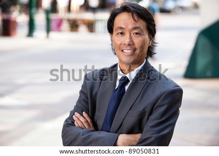 Portrait of an Asian businessman smiling - stock photo