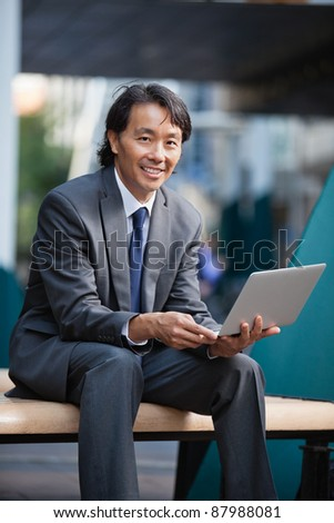 Portrait of an Asian businessman using laptop - stock photo