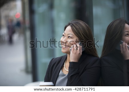 Portrait of an Asian businesswoman standing outside talking on her smart phone.