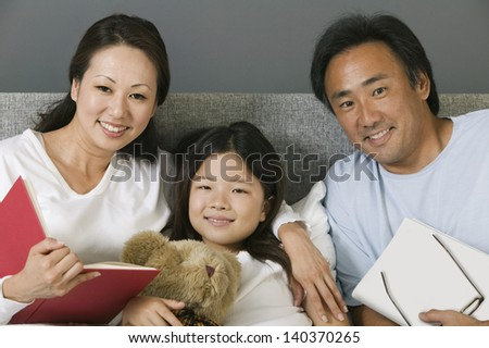 Portrait of an Asian family relaxing together in bed at home