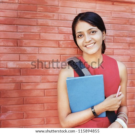 Portrait of an Asian / Indian college student on the red brick wall. - stock photo